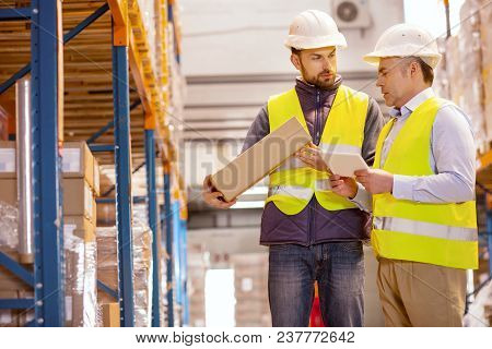 Quality Checking. Nice Professional Manager Talking To His Subordinate While Checking The Boxes With