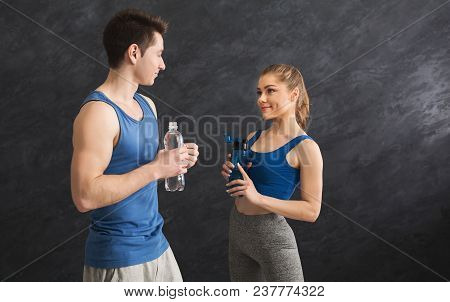 Fitness Couple Having Rest And Talking, Drinking Water At Gym. Smiling Man And Woman Holding Plastic