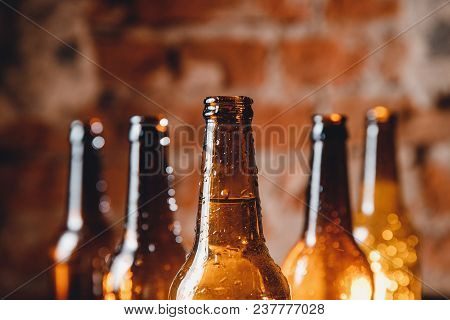 Row Cold Ice Beer Brown Bottles Glass With Drops Of Water Against Brick Wall. Concept Craft Brewery