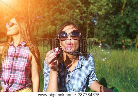Happy Friends In The Park On A Sunny Day . Summer Lifestyle Portrait Of Three Hipster Women Enjoy Ni