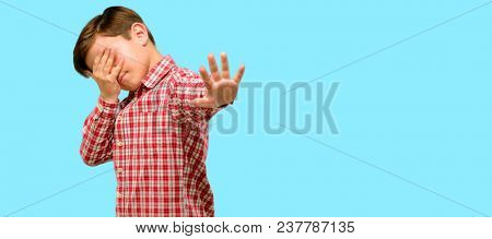 Handsome toddler child with green eyes stressful and shy keeping hand on head, tired and frustrated over blue background