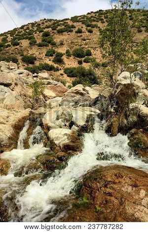 Waterfall On A River With A Riparian Ecosystem Including Rocks, Boulders, Plants, Trees, And Chaparr