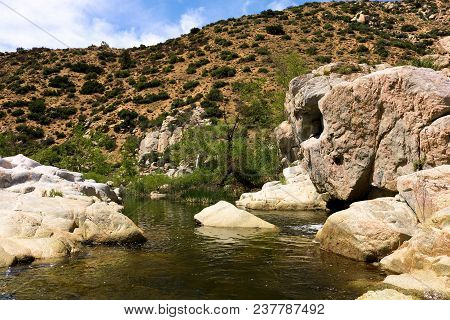 River Surrounded By A Riparian Ecosystem Including Rocks, Boulders, Chaparral Shrubs, Plants, And Tr