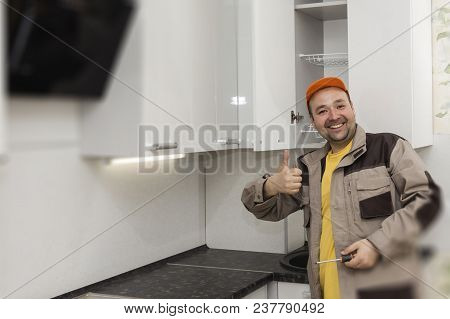 Happy Worker. Assembly Of Kitchen Furniture. Close Up