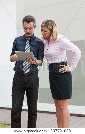 Focused Male And Female Business People Browsing On Tablet Computer Outdoors. Businesspeople Standin