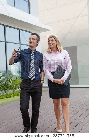 Smiling Aged Male And Female Colleagues Walking And Discussing Idea Outdoors With Building In Backgr