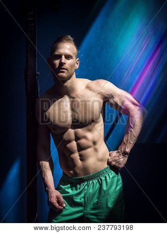 Attractive Shirtless Blond Male Bodybuilder In Shorts Indoors In Dark Gym, Showing Muscular Torso An