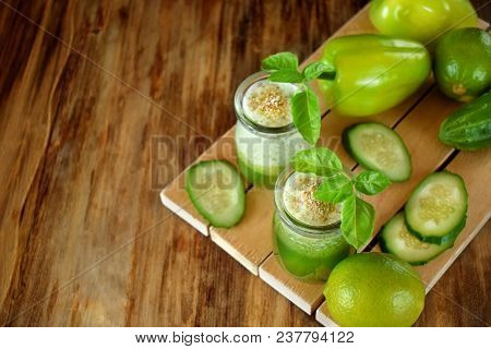 Green Smoothie In Glass Jars Sprinkled With Brans Decorated With Basil On Wooden Background. Top Vie