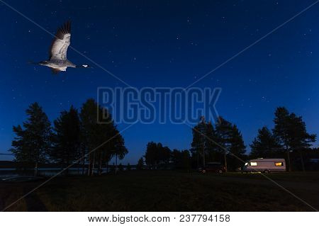 Rural Norrland, Sweden On September 21. View Of A Crane In Flight. Caravan And Car In The Night On S