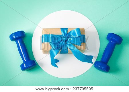 Holiday, Birthday, Party Sport Flat Lay Composition With Blue Dumbbells Gift Box On White Round Circ