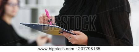 Brunette Woman Hold In Arms Pink Pen And Paper Clipped To Pad Closeup Colleagues In Background. Whit