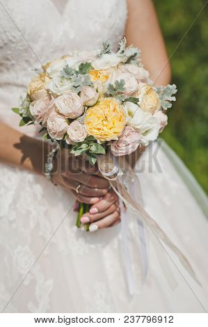 Bouquet Of White And Yellow Roses In Brides Hands.