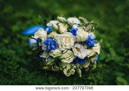 Wedding Bouquet With White Roses And Blue Flowers Lies On A Meadow Of Green Grass