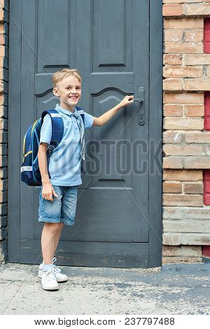 First-grader With A Backpack Is At The Door Of The School. The First Call. End Of The School Year. H