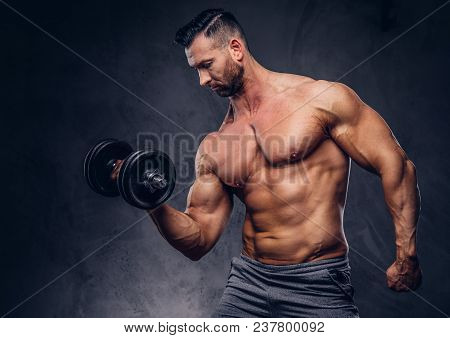 Tall Stylish Shirtless Bodybuilder Dressed In Sports Shorts, Doing Exercise On A Bicep With A Barbel