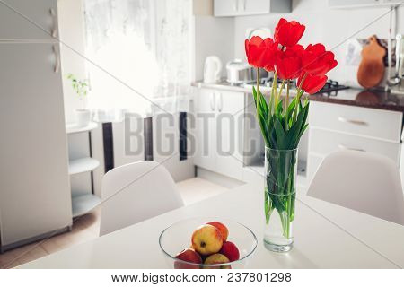 Modern Kitchen Design. Interior Of White And Silver Kitchen Decorated With Flowers. New Cozy Apartme
