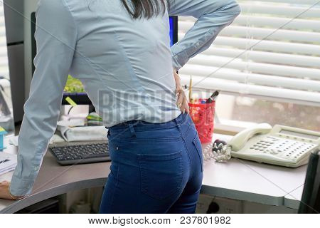 Close-up View Of A Office Worker Woman With Pain In Kidneys. Young Woman With Back Ache Clasping Her