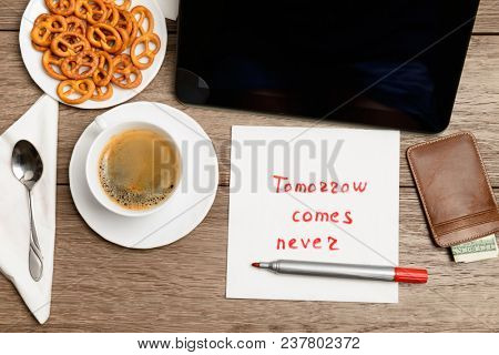 napkin message proverb on wooden table with coffee, some food and tablet PC