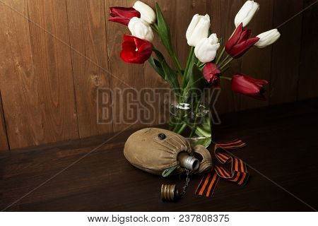 old soldier's flask and St. George's ribbon on dark wooden background, world war memorial symbol for fallen warriors