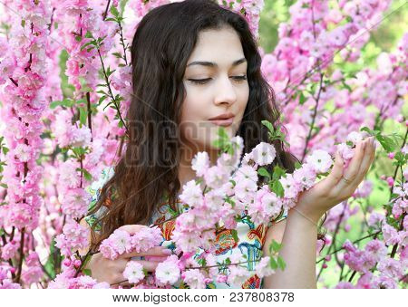 portrait of young girl on pink flowers background, face close up