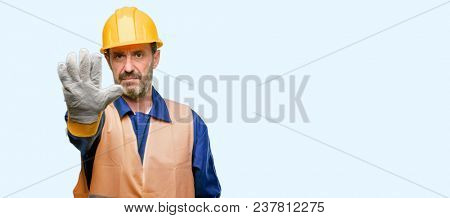 Senior engineer man, construction worker annoyed with bad attitude making stop sign with hand, saying no, expressing security, defense or restriction, maybe pushing isolated over blue background
