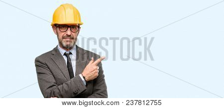 Senior architect or engineer pointing away side with finger isolated over blue background