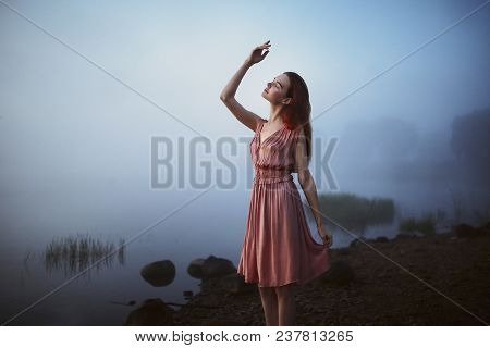 Beautiful Slender Red-haired Model In A Pink Dress Posing Against A Background Of Morning Fog Over T