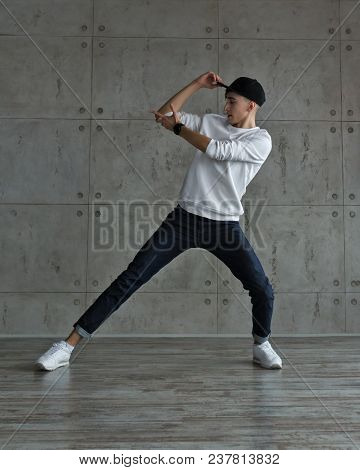 Teenager Guy In Baseball Cap And Sneakers, Jeans And White Sweater Dancing Hip-hop. Dynamics Of Mode