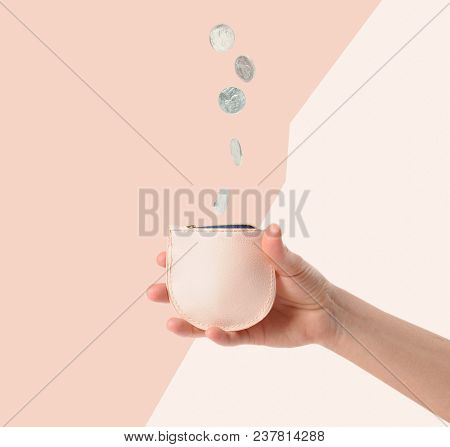 Coins Falling In Wallet. Female Hands Is Putting Coins In Wallet.