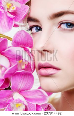 Close-up portrait of a beautiful romantic young woman with flowers. Cosmetics, healthcare. Beauty, fashion concept.