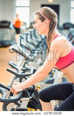 poster of Side view of a determined and beautiful fit woman cycling on stationary bicycle during workout for burning calories at the gym
