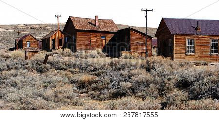 An Old Ghost Town With Desert Brush And Old Telephone Poles Isolated On A White Background.