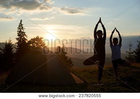 Silhouettes Of Young Mother And Son Doing Gymnastics At The Mountains On Dawn. Tourist Woman And Chi