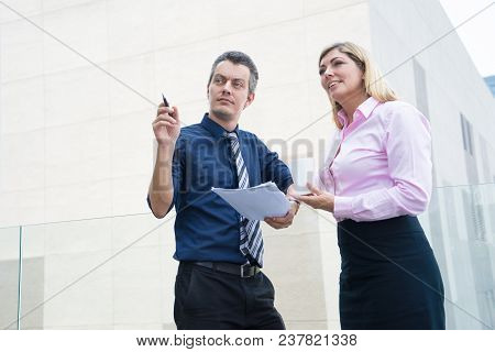 Two Business Partners Looking At Neighbor Building Outdoors. Mid Adult Man Holding Papers And Pointi