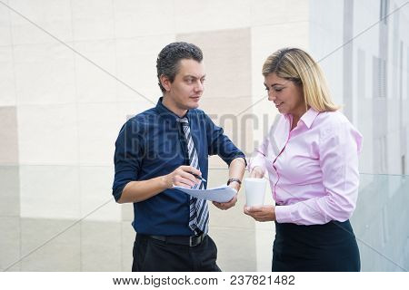 Two Content Office Employees Reviewing Document. Mid Adult Man In Tie Pointing Pen At Paper, Woman I
