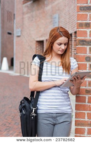 Portrait of a student working with a tablet computer outside a building