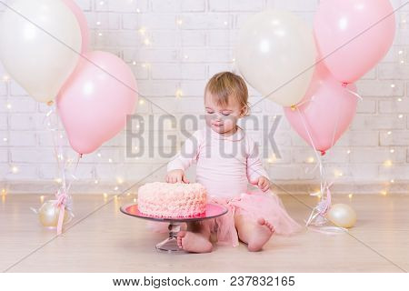 Birthday Celebration Concept - Happy Little Girl With Cake Over Brick Wall Background With Lights An