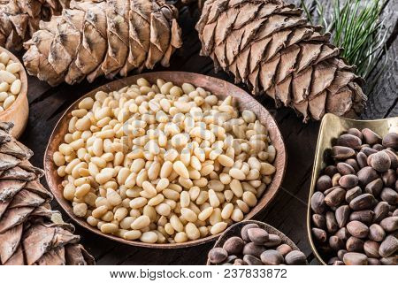 Pine nuts in the bowl and pine nut cones on the wooden table. Organic food.