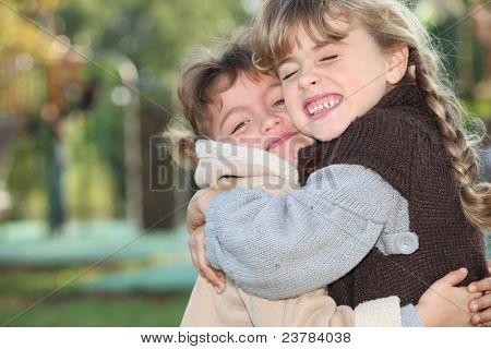 Young girls hugging outside