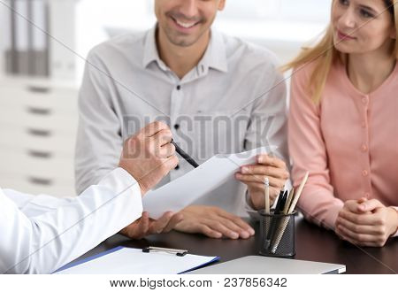 Male doctor consulting young couple in clinic
