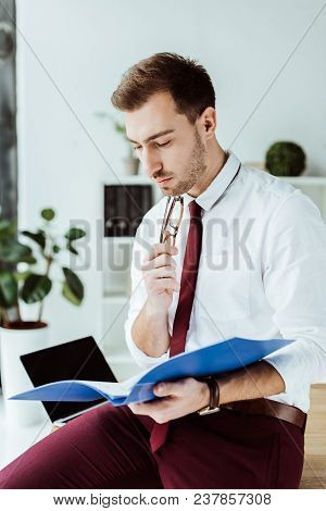 Pensive Business Man Reading Documents From Folder
