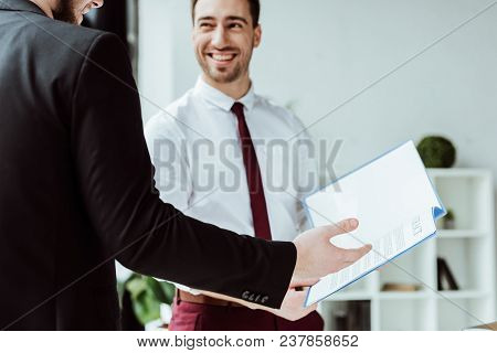 Businesspeople Working With Documents In Modern Office