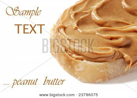 Creamy swirls of peanut butter on freshly baked homemade bread.  Macro on white background with copy space.