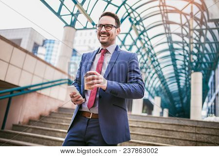 Businessman Using Mobile Phone Outside Of Office Buildings In The Background. Young Caucasian Man Ho