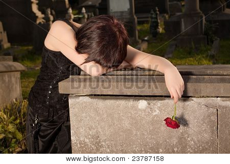 Halloween woman in gothic dress crying on a tomb