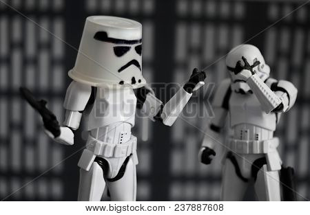 DEC 12 2017: Humorous image of Star Wars Imperial Stormtroopers, one has a replacement helmet / bucket while the other face palms with embarrassment - Hasbro Black Series Action Figures