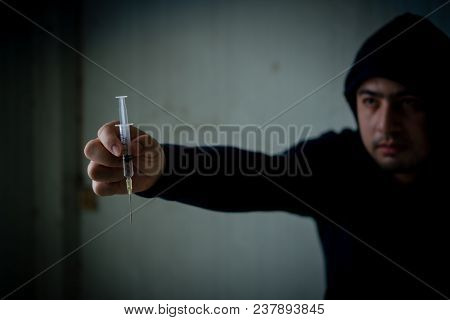 Teenagers Wearing Black Hoods Look Like They Are Addicted. Holding The Syringe. Selected Focus.