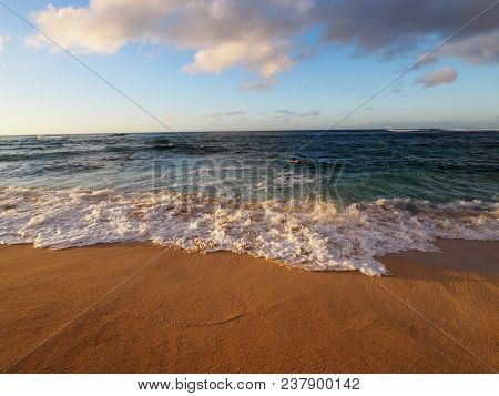 Sea Foam Forms As Waves Move Into Beach Shore Looking Into The Pacific Ocean On The North Shore Of O
