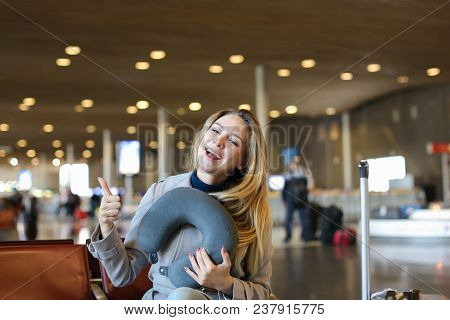 European Pretty Woman Sitting With Neck Pillow And Valise In Airport Waiting Room. Concept Of Travel