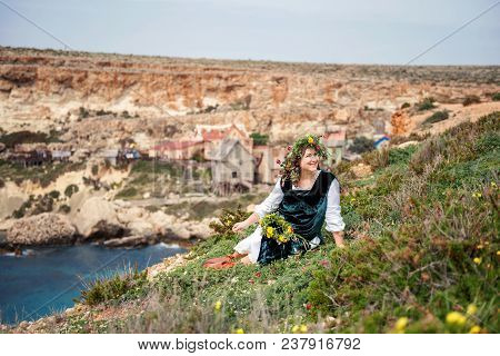 An Attractive Plump Woman Sits On A Grassy Slope Above The Sea In Retro Ethnic Ethnic Clothes And A